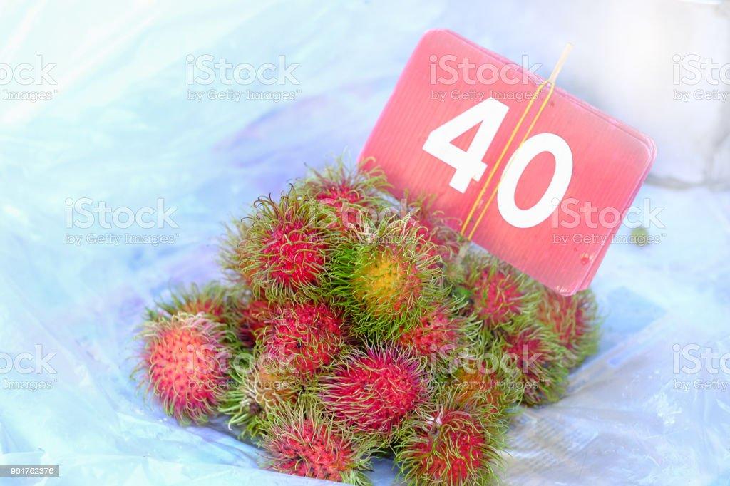 Rambutan sweet delicious fruit fruit 40 Thai baht per kilogram on white background in local market Asia royalty-free stock photo