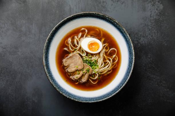 牛肉の舌肉と ajitama のスープで、濃い背景にボウルに卵を漬けたラーメンアジア麺 - ラーメン ストックフォトと画像