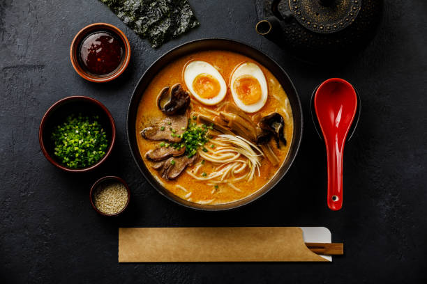 Ramen asian noodle in broth with Beef tongue meat, mushroom and Ajitama pickled egg in bowl on dark background stock photo