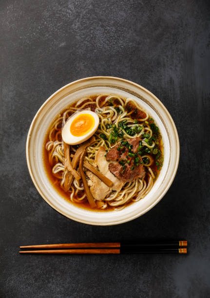 Ramen asian Noodle in broth with Meat and Ajitama pickled Egg in bowl on dark background stock photo