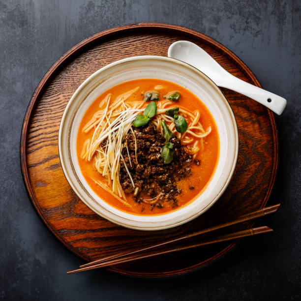 Ramen asian noodle in broth with minced chicken in soy paste and leek on dark background stock photo