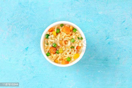 Ramen cup, instant noodles in a plastic cup, overhead shot on a blue background