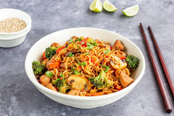 ramen noedels met broccoli, paprika en kip in een kom met stokjes - aziatische noedels stockfoto's en -beelden