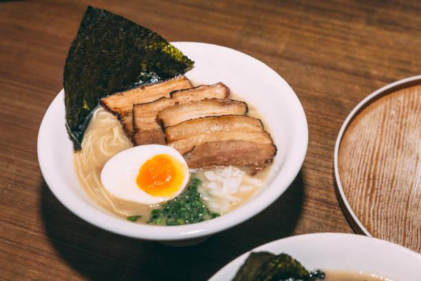 ramen varkensvlees bot soep (tonkotsu ramen) met chashu varkensvlees, lente-ui, sprout, ui, mma en gedroogd zeewier. - ramen noedels stockfoto's en -beelden