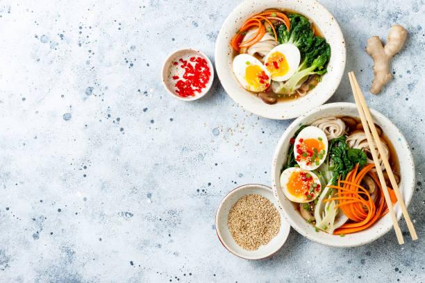 ramen traditionele japanse noodle soep met eieren, pak choi kool, vleesbouillon, wortel, champignons in kom op lichtgrijs achtergrond. aziatische stijl eten. - japanse gerechten stockfoto's en -beelden