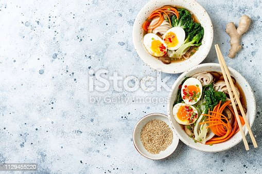 Ramen traditional japanese noodle soup with eggs, pak choi cabbage, meat broth, carrot, mushrooms in bowl on light grey background. Asian style food.