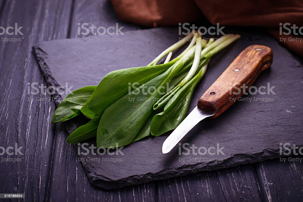 Ramson and knife on slate background stock photo