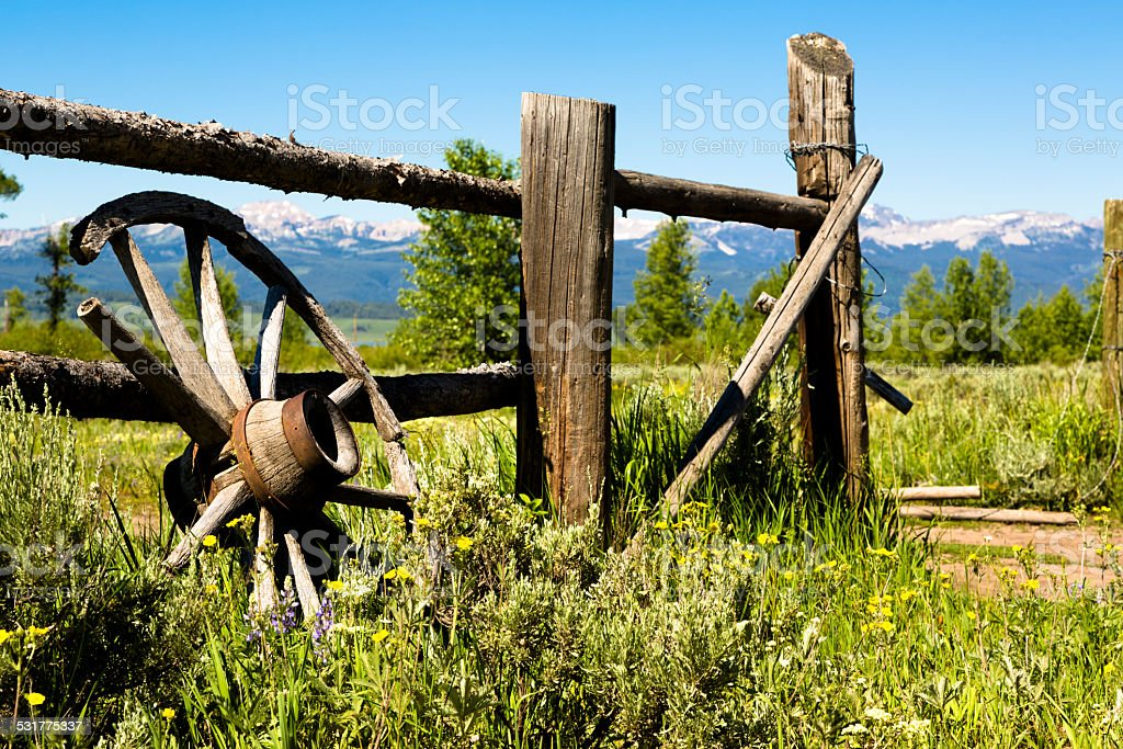 Ranch: Old weathered wagon wheel against worn wooden fence. Mountains. stock photo