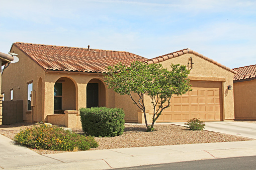 Tucson, Arizona, USA - April 7, 2017:  New ranch, gold and mustard yellow stucco home in Tucson, Arizona, USA with beautiful blue sky and landscaping.