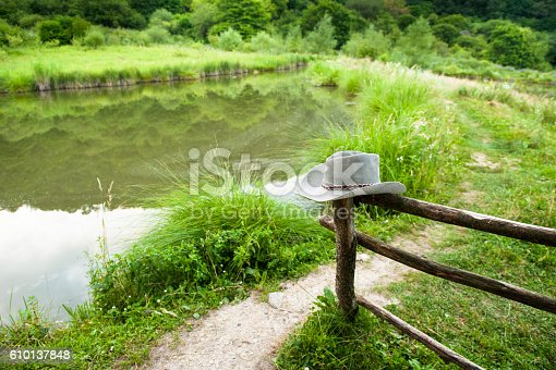 ranch with wooden fence, cowboy hat, footpath, pond and vegetation