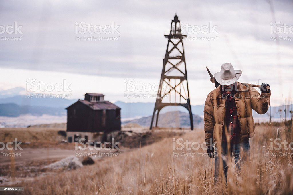 Rancher carries pickaxe through western field mountains in distance stock photo