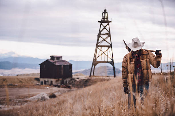 Rancher carries pickaxe through western field mountains in distance Rancher carries pickaxe over should while walking through western field mountains in the distance rancher stock pictures, royalty-free photos & images