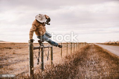 Ranching worker jumps over barbwire fence while holding binoculars in order to get to back road.