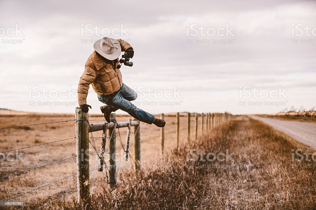 Rancher jumps over barbed wire fence to get to road stock photo