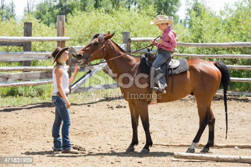Rancher teaching young son to ride horse