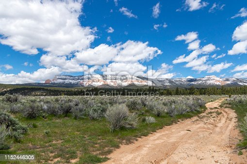 This is wide open ranchland near Escalante Utah.  A dirt road leads to a  snow covered rock formation in the distance.