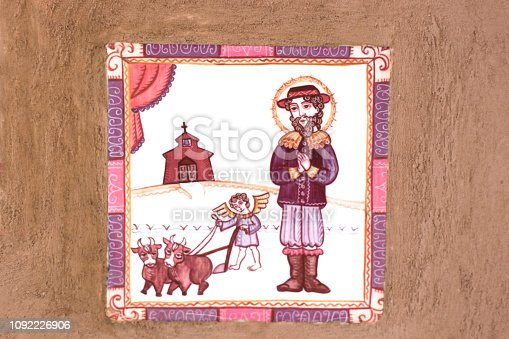 Ranchos de Taos, NM: Traditional tile on brown adobe wall showing rural/religious scene. Some copy space available.