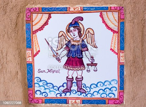 Ranchos de Taos, NM Style: Traditional tile on a brown adobe wall showing San Miguel (the archangel Michael). Close-up shot.