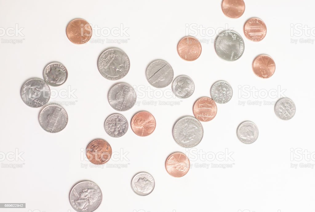 Random US coins scattered on a white background. stock photo