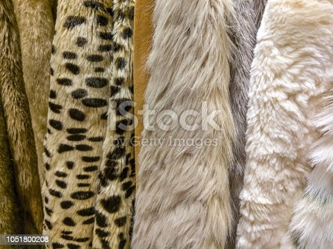 A range of fur coats on hangers.
