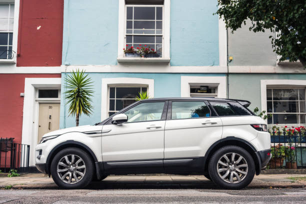 Range Rover Evoque parked on a London street London, UK - Side view of a white Range Rover Evoque, parked on a street of pastel coloured homes. range rover stock pictures, royalty-free photos & images