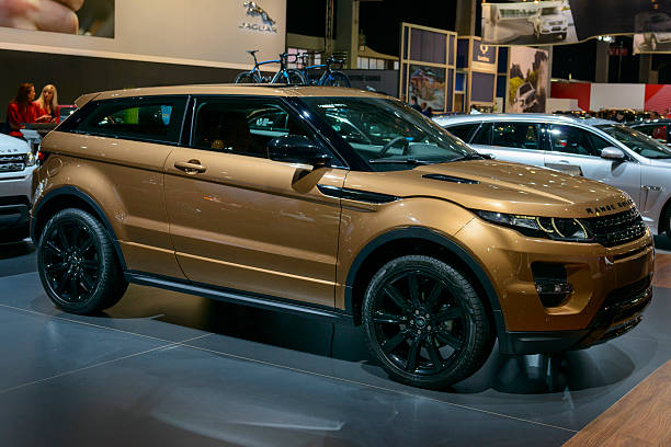 Range Rover Evoque Brussels, Belgium - January 14, 2014: Bronze Range Rover Evoque compact SUV on display at the 2014 Brussels motor show. Two girls are sitting behind a desk in the background. range rover stock pictures, royalty-free photos & images