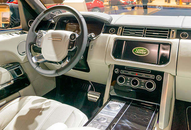 Range Rover luxury interior with leather and wood Brussels, Belgium - January 15, 2015: Range Rover luxury interior on display during the 2015 Brussels motor show. People in the background are looking at the cars. range rover stock pictures, royalty-free photos & images