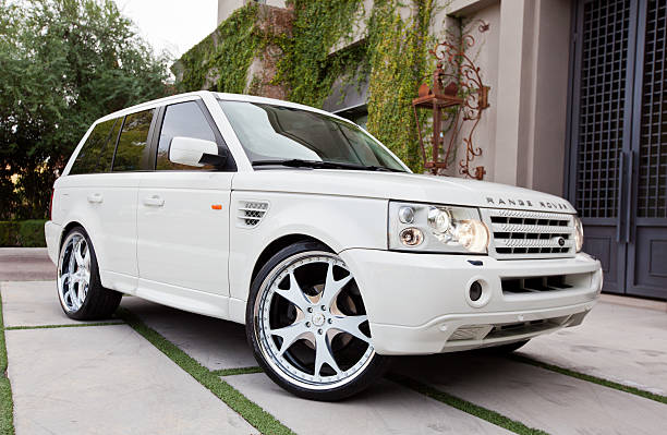 Range Rover Scottsdale, United States - November 29, 2011: A photo of a parked white Range Rover SUV. The Range Rover although designed for off road use, has become popular as a luxury street vehicle. range rover stock pictures, royalty-free photos & images
