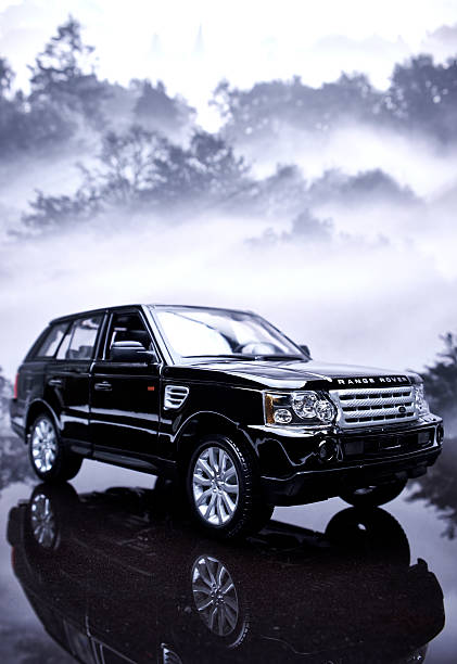 Range Rover Sport Model Beaconsfield, UK - December 8, 2015: A vertical image featuring a 1/18 scale model of a black Range Rover Sport. The model car is photographed in a studio setting, and is sitting on a reflective black background against a background image of trees on a foggy morning. range rover stock pictures, royalty-free photos & images