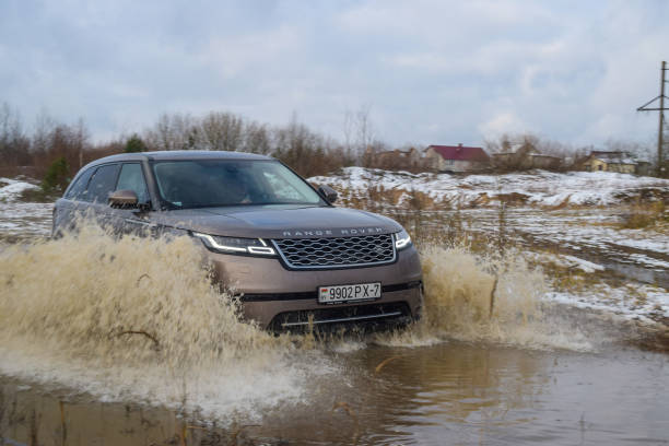 Range Rover Velar Minsk, Belarus - November 7, 2017: Range Rover Velar at a test-drive crosses deep puddle. Velar splashes through that large puddle on the side of the road. range rover stock pictures, royalty-free photos & images