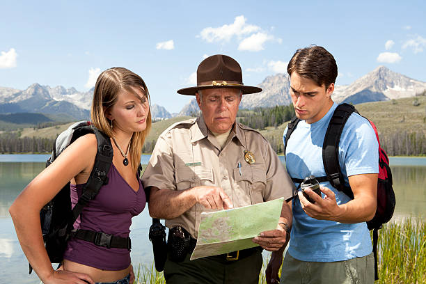 Ranger Helps Lost Campers Ranger Helps Lost Campers. This stock image has a horizontal composition. park ranger stock pictures, royalty-free photos & images
