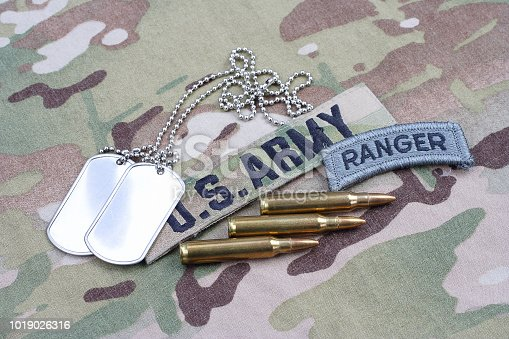 istock US ARMY ranger tab, flag patch,  with dog tag and 5.56 mm rounds on camouflage uniform 1019026316