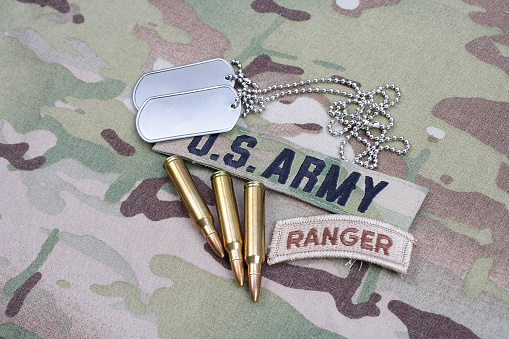istock US ARMY ranger tab, flag patch,  with dog tag and 5.56 mm rounds on camouflage uniform 1019030684