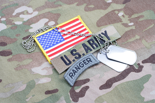 istock US ARMY ranger tab, flag patch,  with dog tag on camouflage uniform 1019025888