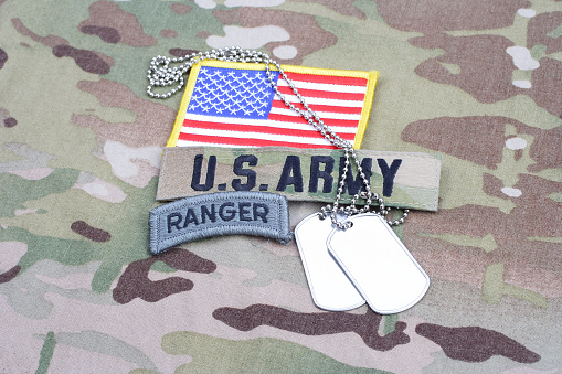 istock US ARMY ranger tab, flag patch, with dog tag on camouflage uniform 1190926069