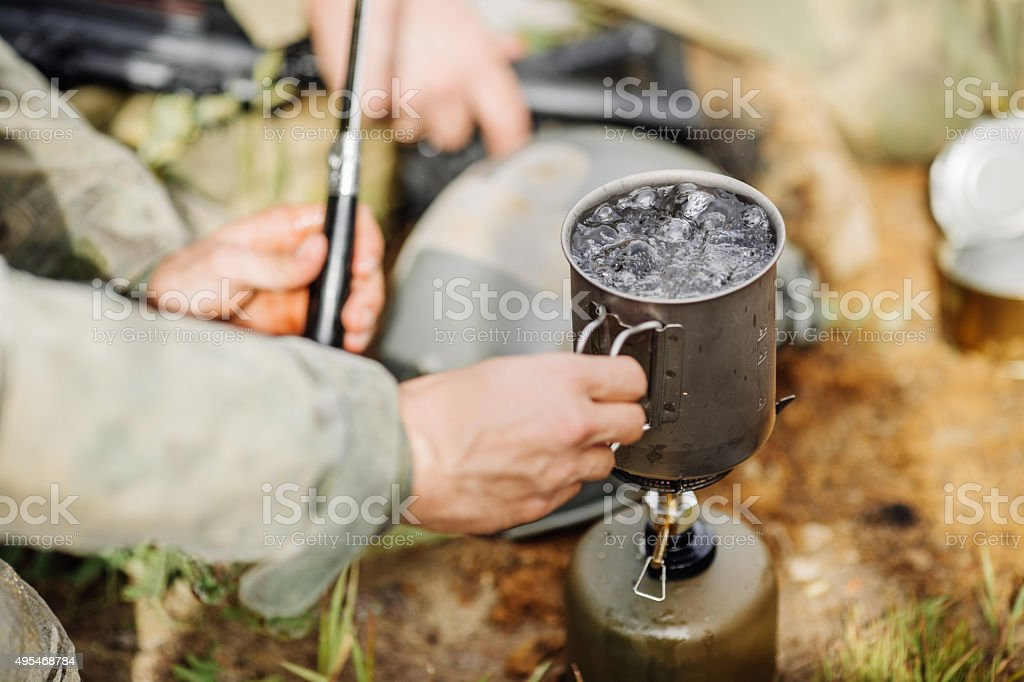 rangers are heated food on the fire and eat stock photo