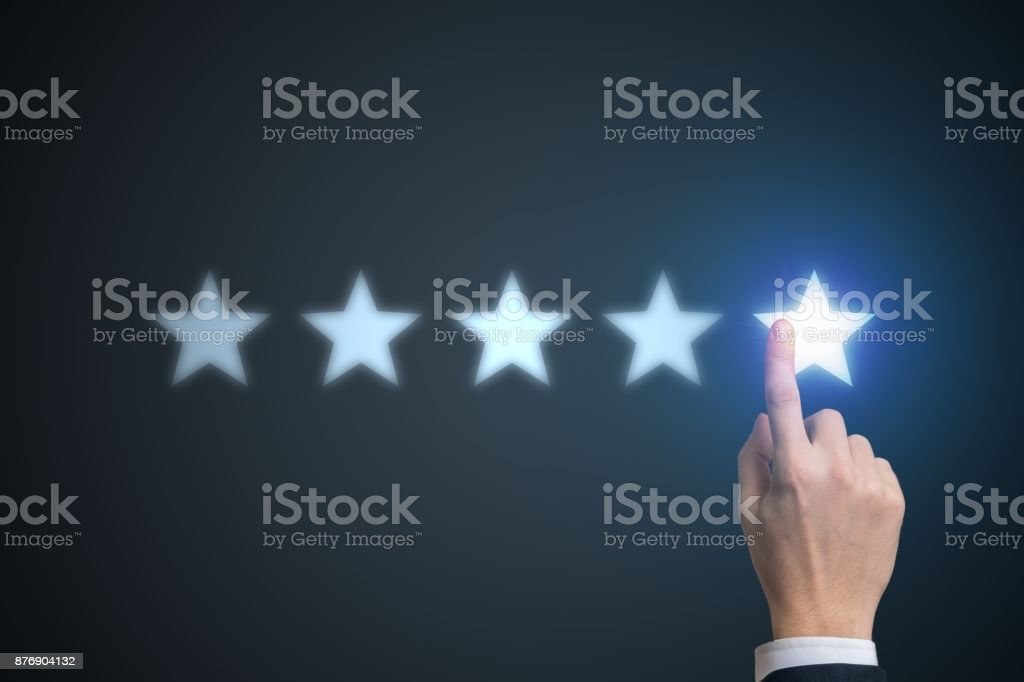 Ranking concept. Human hand is rating with 5 stars. stock photo
