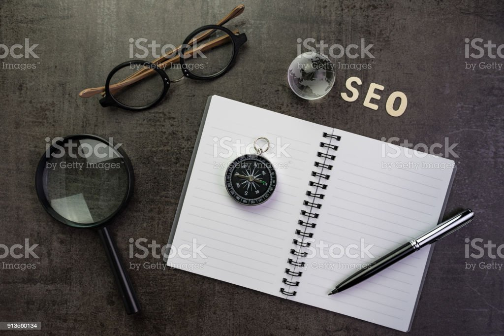 SEO ranking idea, search engine optimization concept with decoration globe, alphabet SEO and compass on white notebook with pen and eyeglasses dark cement chalkboard background stock photo