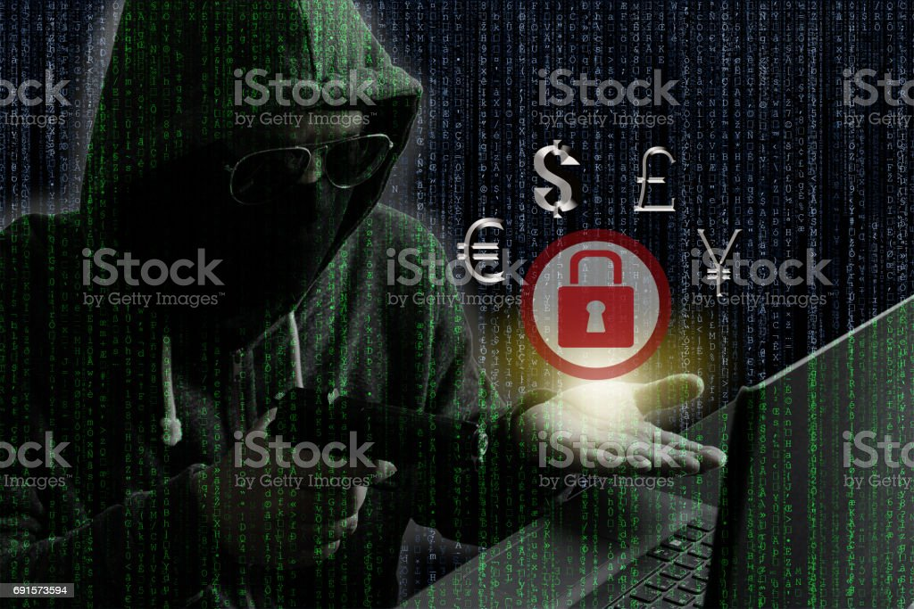 Ransomware concept : Hacker/Cyber criminal pointing gun into laptop computer as if demanding money from opposite site in exchange for unlocking computer. stock photo