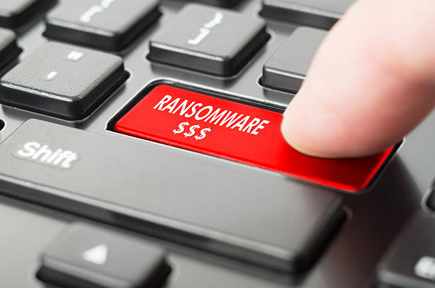 Ransomware written on keyboard button with finger pressing on it – Foto
