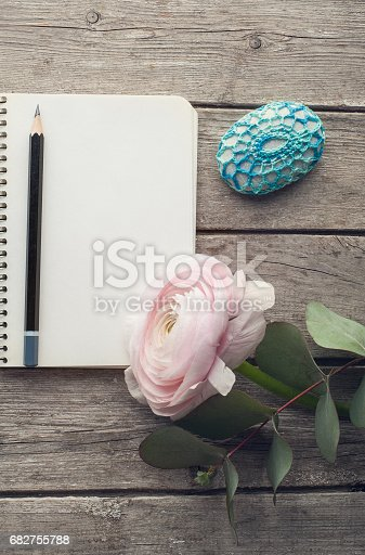 Overhead shot of ranunculus and paperweight over wood table top with an open journal. Flat lay top view style.