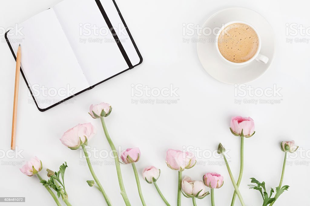 Ranunculus flowers, empty notebook and cup of coffee. Flat lay. stock photo