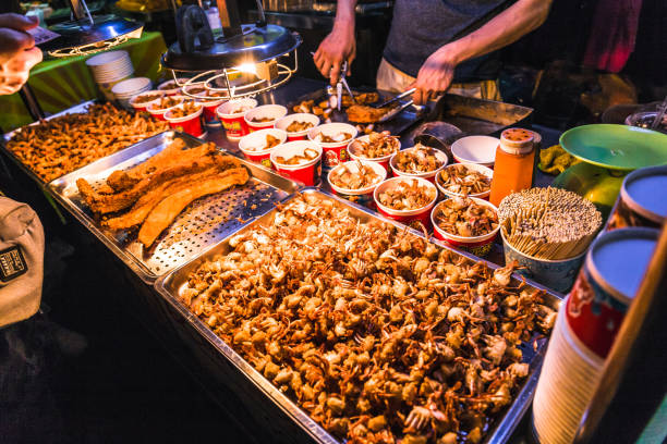 Raohe night market Taipei, Taiwan - June 21, 2018: This snack food is a squid which is deep fried till golden brown and extremely crispy. The squid is lightly coated with salt and pepper at the Raohe night market. night market stock pictures, royalty-free photos & images