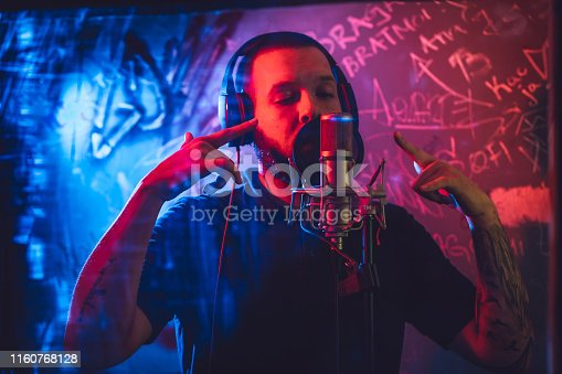 Young caucasian male rap musician singing in studio in deaf room.