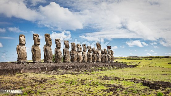 Easter Island Ahu Tongariki Panorama. Fifteen ancient civilization polynesian Moai Statues standing side by side in a row along the pacific ocean coast under sunny blue summer sky with fluffy cloudscape. Rapa Nui. Easter Island, Isla de Pascua, Polynesia, Chile, Oceania