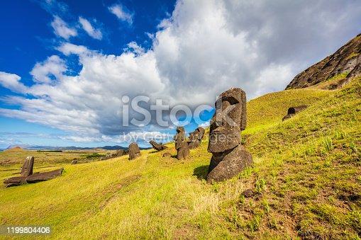 Rano Raraku Easter Island Moai Statues under sunny summer cloudy sky. Rano Raraku, Rapa Nui National Park, Hanga Roa, Easter Island, Isla de Pascua, Polynesia, Chile, Oceania