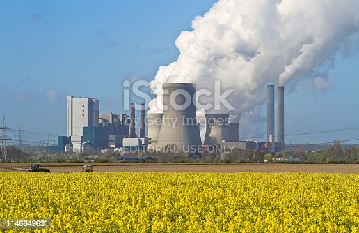 Bergheim, Germany - April 20, 2016: Yellow rapeseed field in front of a lignite-fired power station under a blue sky