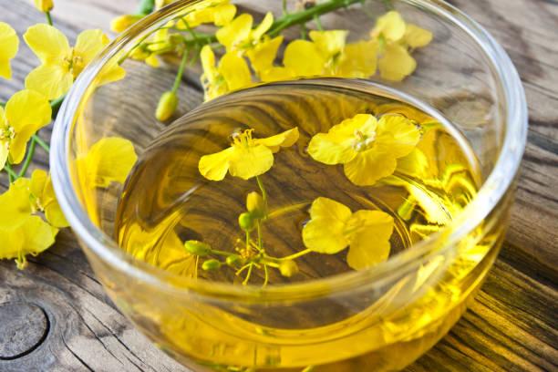 Rapsöl und Glasschale mit Blüten – Foto