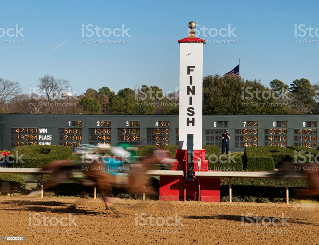 Rapid motion photo of horses at a race track finish line stock photo