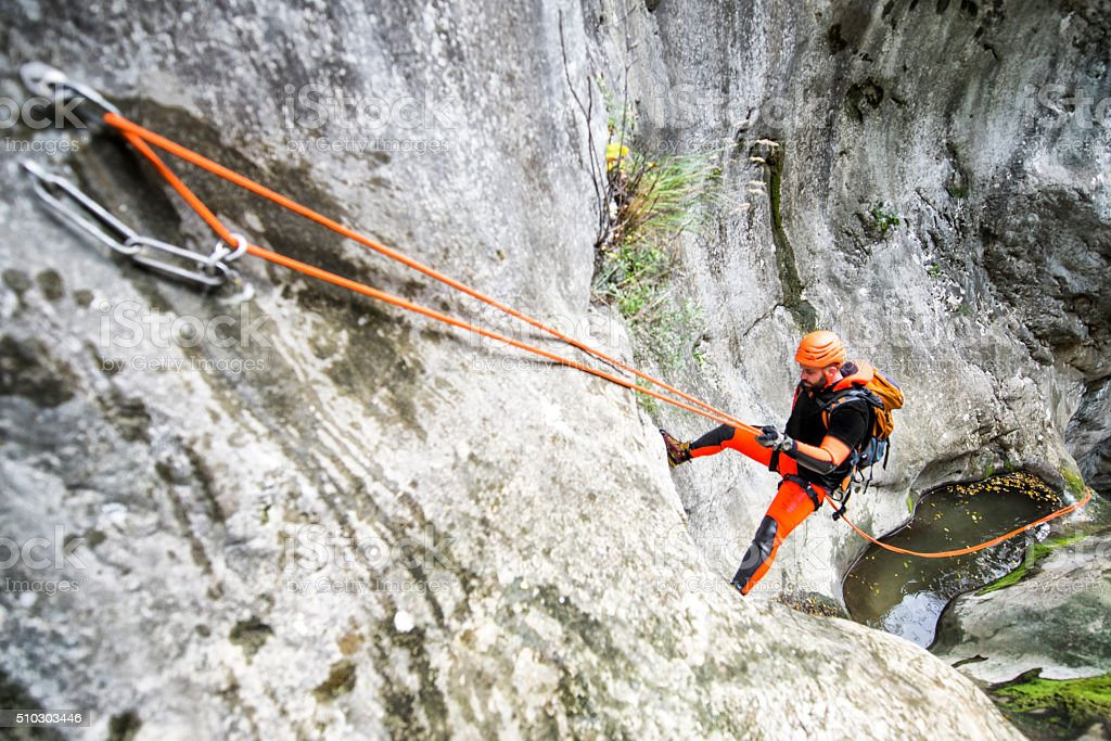 Rappeling down the cliff stock photo
